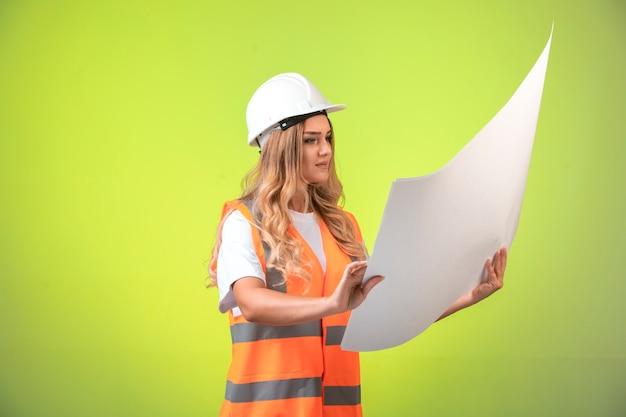 Vrouwelijke ingenieur in witte helm en vistuig die het bouwplan controleert en het leest.