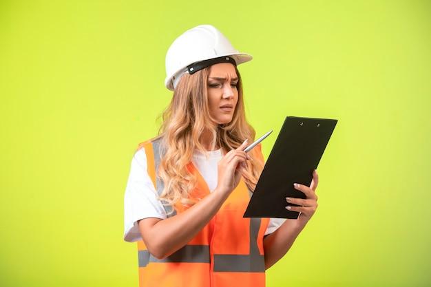 Vrouwelijke ingenieur in witte helm en vistuig die het rapport controleert.