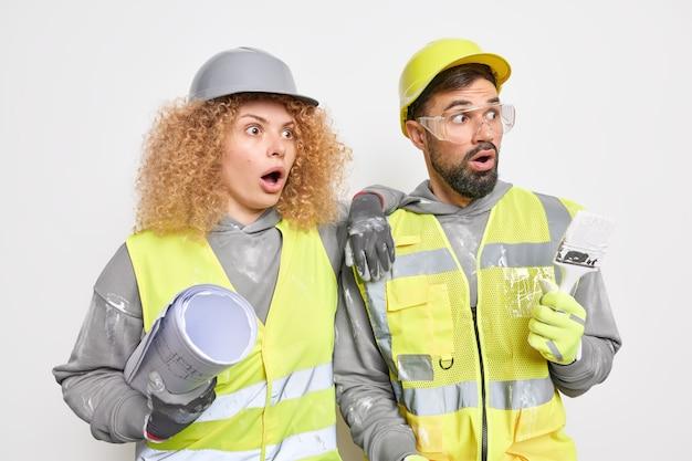 Vrouwelijke ingenieur kijkt geschokt weg, gekleed in uniform, houdt blauwdruk en schilderpenseel vast