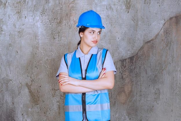 Vrouwelijke ingenieur met blauwe helm en uitrusting en kruisende armen om professionele poses te geven.