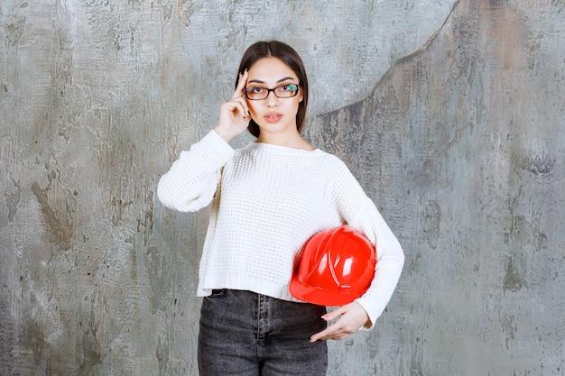 Vrouwelijke ingenieur met een rode helm en ziet er attent uit of heeft een goed idee.
