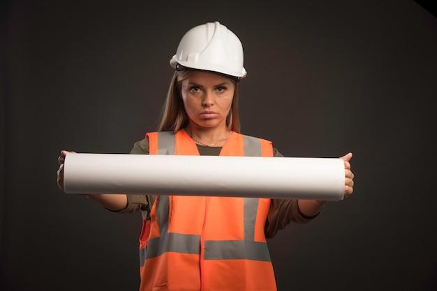 Vrouwelijke ingenieur met een witte helm die het projectplan aanbiedt en er gemotiveerd uitziet.