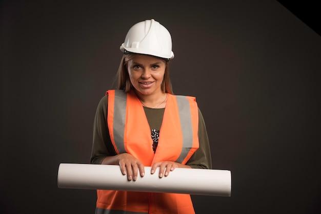 Vrouwelijke ingenieur met een witte helm die het projectplan aanbiedt en er professioneel uitziet.