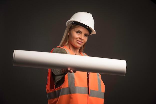 Vrouwelijke ingenieur met een witte helm die het projectplan aanbiedt en er zelfverzekerd uitziet.