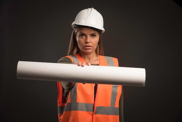 Vrouwelijke ingenieur met een witte helm die het projectplan aanbiedt.