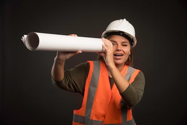 Vrouwelijke ingenieur met een witte helm die het projectplan vasthoudt en er doorheen kijkt.