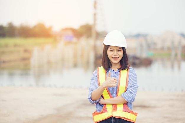 Vrouwelijke ingenieur met helm duim opdagen als ok teken op bouwplaats. kracht van vrouwen, gendergelijkheid, werkende vrouwen, zelfverzekerde vrouwelijke ingenieur