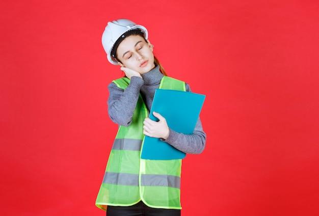 Vrouwelijke ingenieur met witte helm die een blauw projectdossier vasthoudt en ziet er slaperig uit.