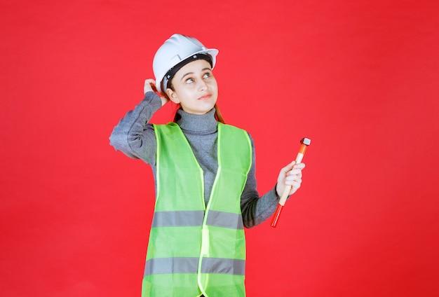 Vrouwelijke ingenieur met witte helm die een houten bijl vasthoudt en nadenkt over hoe deze te gebruiken.
