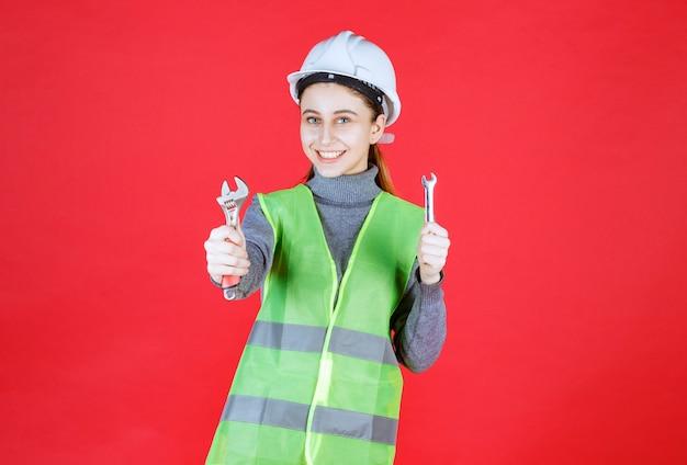 Vrouwelijke ingenieur met witte helm die een metalen moersleutel vasthoudt en deze aan haar collega geeft.