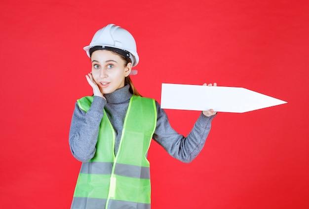 Vrouwelijke ingenieur met witte helm die een pijl naar rechts houdt en er verward uitziet.