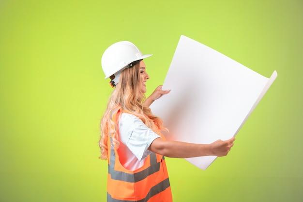 Vrouwelijke ingenieur projectplan lezen.