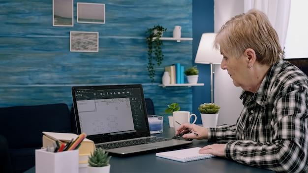 Vrouwelijke ingenieur van middelbare leeftijd die werkt met cad-software voor architectuurplannen op laptopcomputerontwerper...