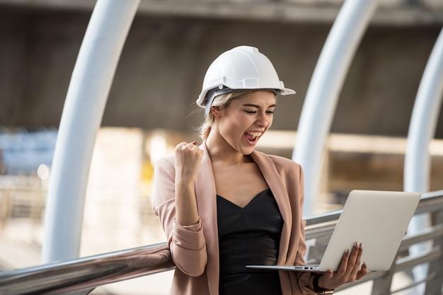Vrouwelijke ingenieur viert met laptop