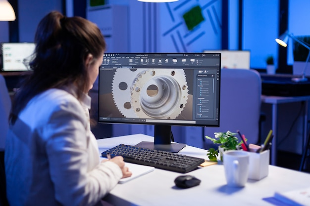 Vrouwelijke ingenieur werkt 's avonds laat aan een nieuw digitaal prototype met behulp van professionele bouwmachines bij een kantoorbedrijf