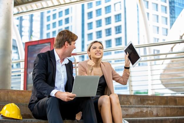 Vrouwelijke ingenieur with colleague holding digital tablet tegen bouwwerf
