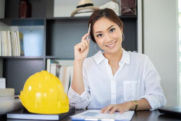 Vrouwelijke ingenieurs denken aan nieuwe banen en glimlachen en werken gelukkig