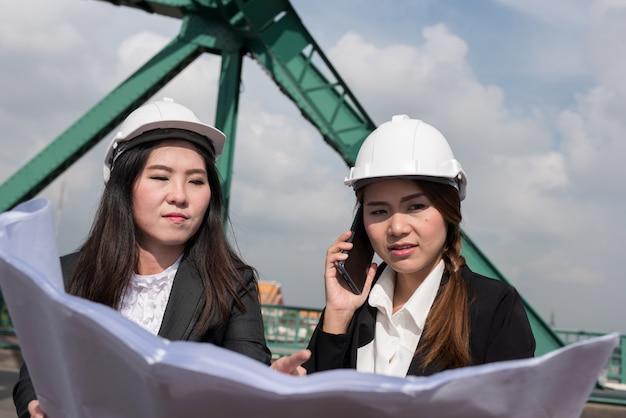 Vrouwelijke ingenieurs houden radio, blauwdrukken en rapporten, controleschema's voor werknemers in de energiesector.