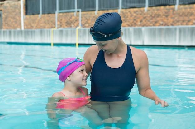 Vrouwelijke instructeur en jong meisje ontspannen in het zwembad