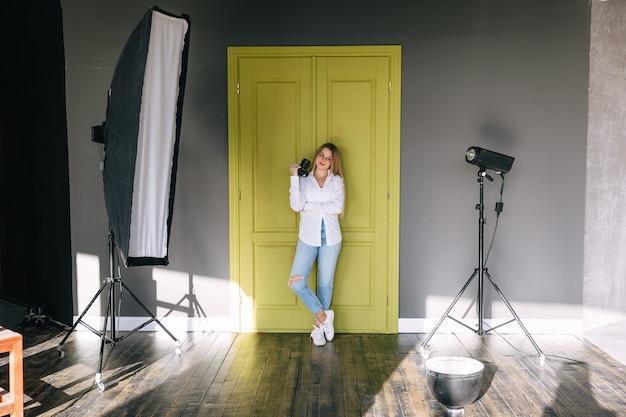 Vrouwelijke instructeur voor fotografielessen staat met camera in handen en lichte apparatuur in de buurt