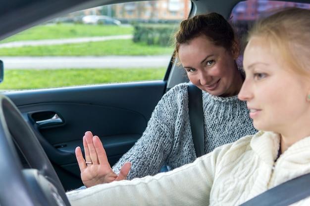 Vrouwelijke instructeur zwaait vriendelijk de hand tijdens een rijles met een vrouwelijke student