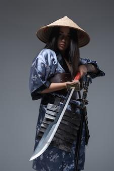 Vrouwelijke japanse krijger gekleed in bamboe hoed en kimono met zwaard.