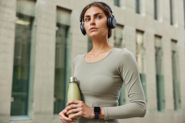Vrouwelijke jogger houdt fles vers water vast heeft fitnesstraining buitenshuis luistert muziek via koptelefoon draagt casual jumper smartwatch op arm poseert op modern gebouw