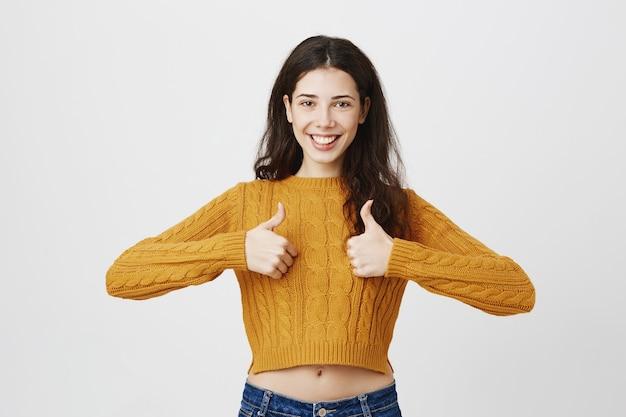 Vrouwelijke jonge ondernemer met thumbs-up in goedkeuring, eens of iets leuks, lof keuze