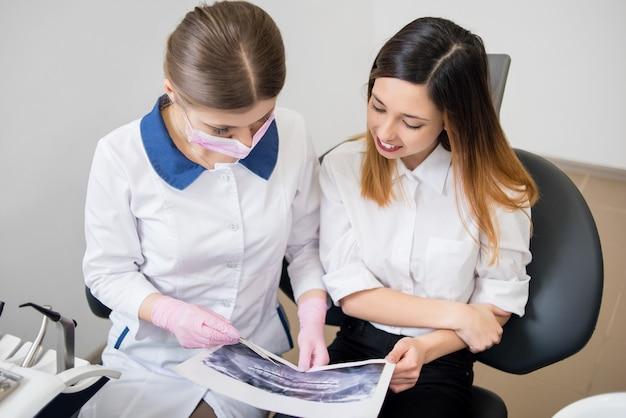 Vrouwelijke jonge tandarts die met vrouwelijke patiënt in tandkliniek spreekt, x-ray beeld onderzoekt en voor tandprocedures voorbereidingen treft. tandheelkunde