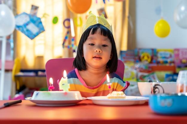 Vrouwelijke jongen met verjaardagstaart en kaars