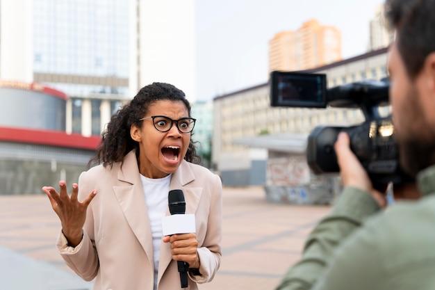 Vrouwelijke journalist die het nieuws buiten vertelt