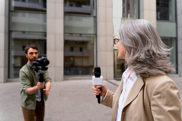 Vrouwelijke journalist neemt een interview naast haar cameraman