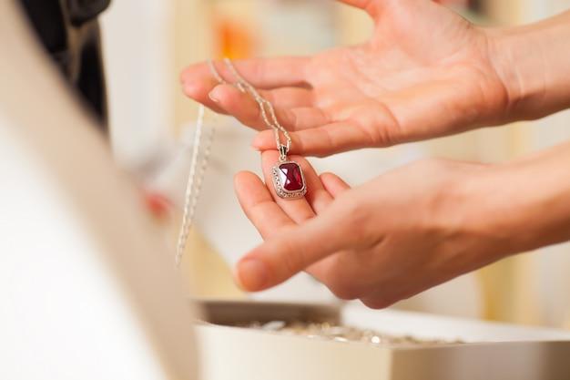 Vrouwelijke juwelier die juwelen presenteert