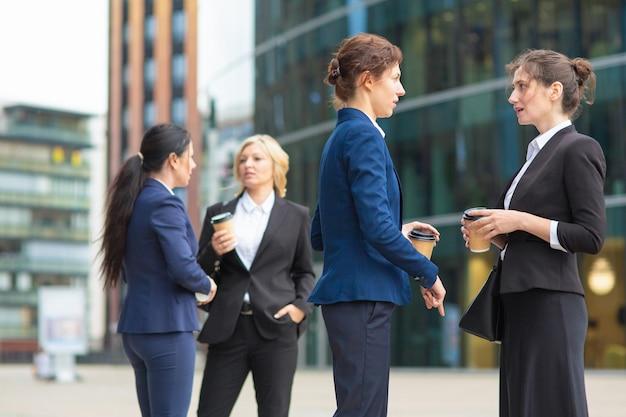 Vrouwelijke kantoor collega's met afhaalmaaltijden papieren bekers staan buiten, koffie drinken, praten, project bespreken of chatten. gemiddeld schot. koffiepauze concept