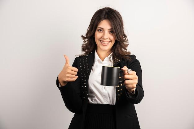 Vrouwelijke kantoormedewerker biedt een kopje thee aan en geeft duimen omhoog