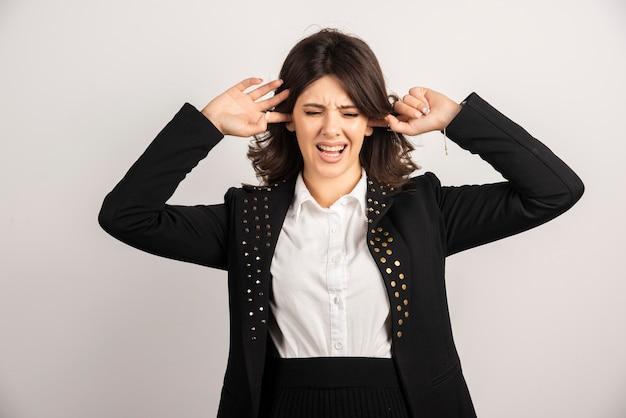 Vrouwelijke kantoormedewerker die haar oren bedekt vanwege lawaai