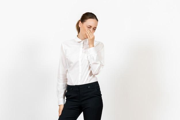 Vrouwelijke kantoormedewerker in elegante witte blouse die haar neus op wit bedekt