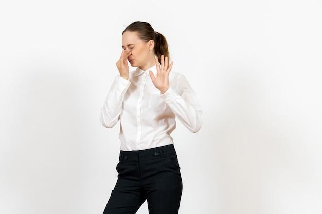 Vrouwelijke kantoormedewerker in elegante witte blouse die haar neus op wit sluit