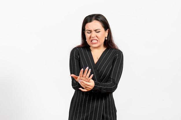 Vrouwelijke kantoormedewerker in strikt zwart pak hur haar arm op wit
