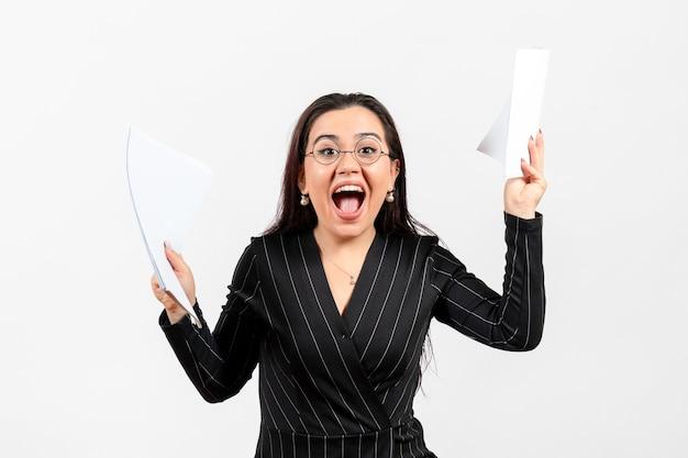 Vrouwelijke kantoormedewerker in strikt zwart pak met documenten op wit