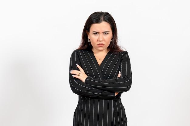 Vrouwelijke kantoormedewerker in strikt zwart pak met een boos gezicht op wit