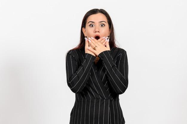 Vrouwelijke kantoormedewerker in strikt zwart pak met geschokt gezicht op wit