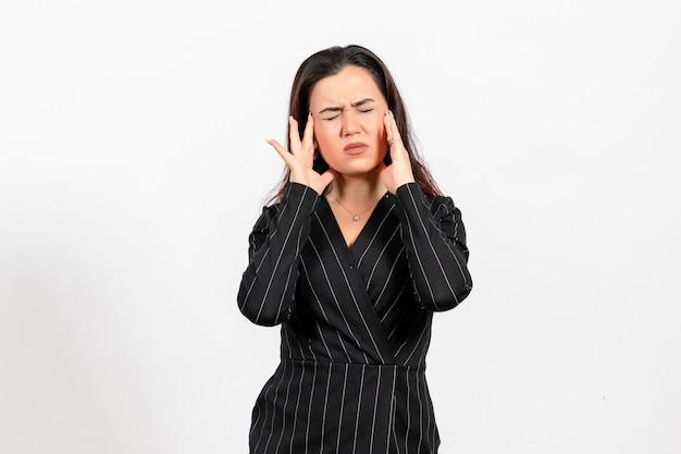 Vrouwelijke kantoormedewerker in strikt zwart pak met hoofdpijn op wit