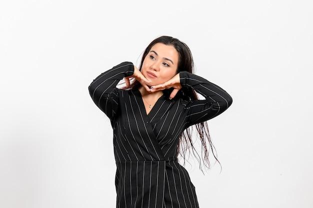 Vrouwelijke kantoormedewerker in strikt zwart pak poseren op wit