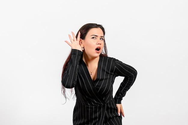 Vrouwelijke kantoormedewerker in strikt zwart pak probeert goed te luisteren op wit