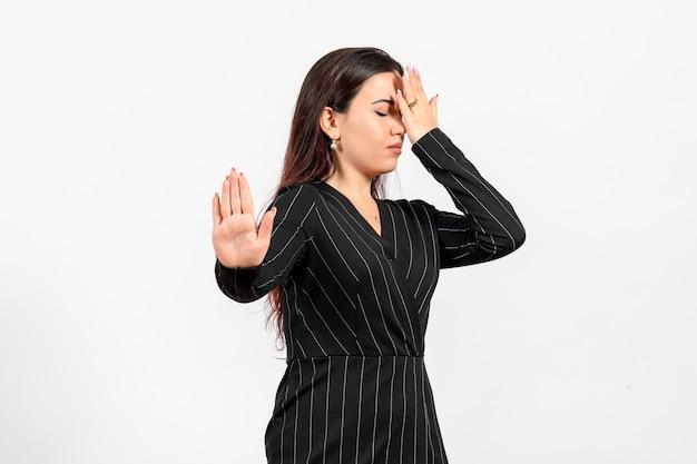 Vrouwelijke kantoormedewerker in strikt zwart pak wil niet op wit kijken