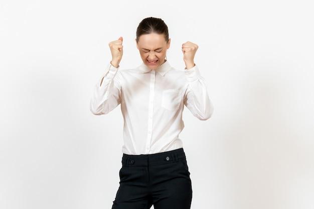 Vrouwelijke kantoormedewerker poseren en boos voelen in witte blouse op wit