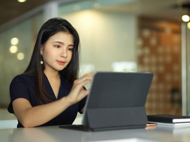 Vrouwelijke kantoormedewerker werken met digitale tablet in kantoorruimte