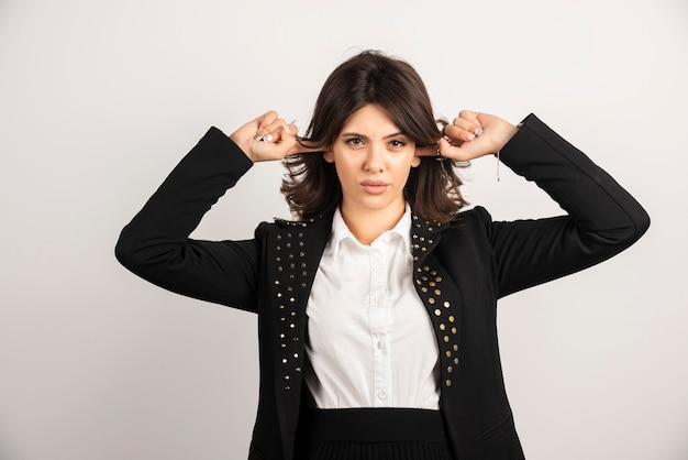 Vrouwelijke kantoormedewerker wijzend naar haar hoofd op wit