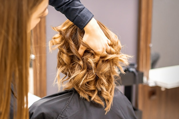 Vrouwelijke kapper controleert bruin krullend kapsel van een jonge blanke vrouw in schoonheidssalon